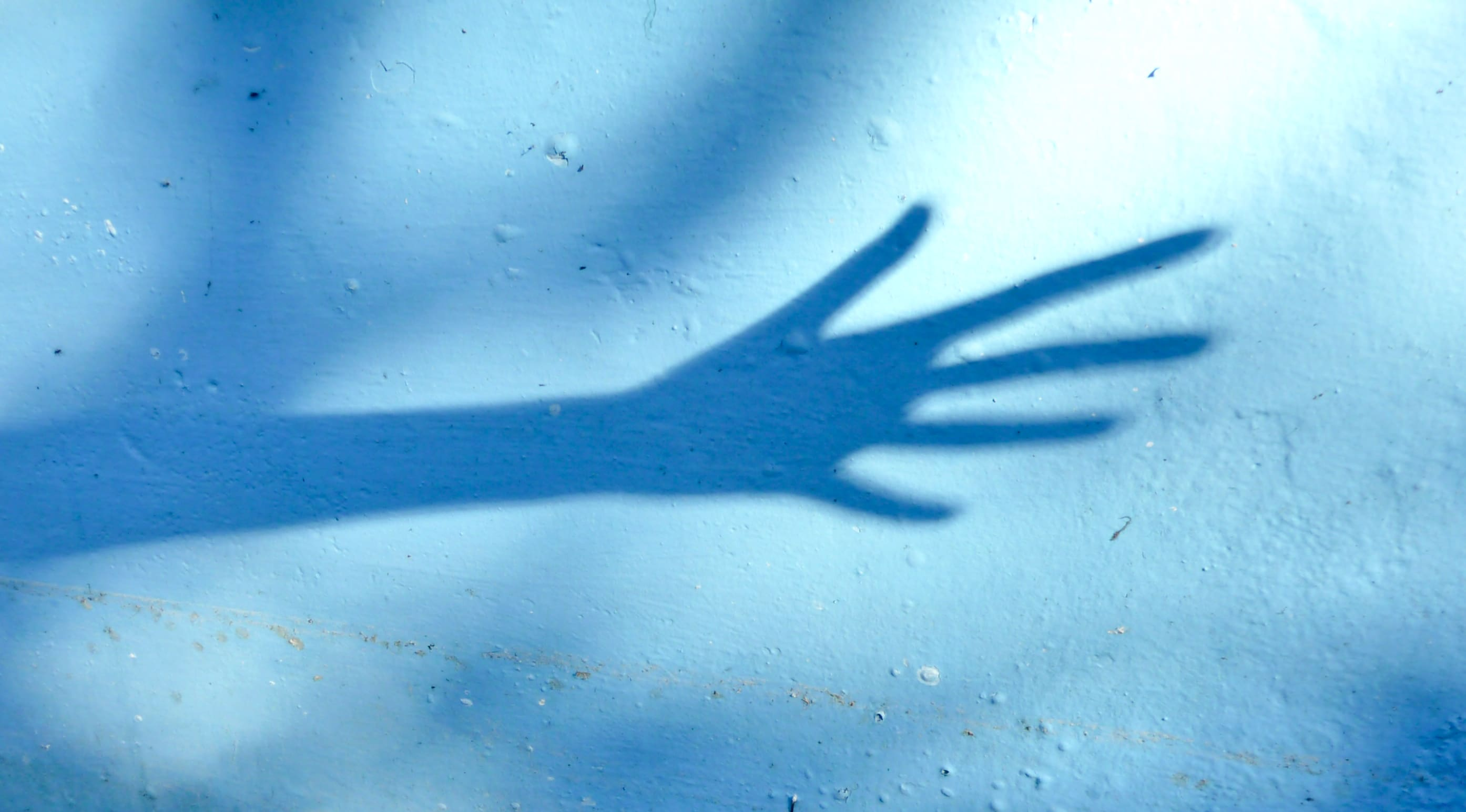 A shadow of an outstretched arm against a blue wall