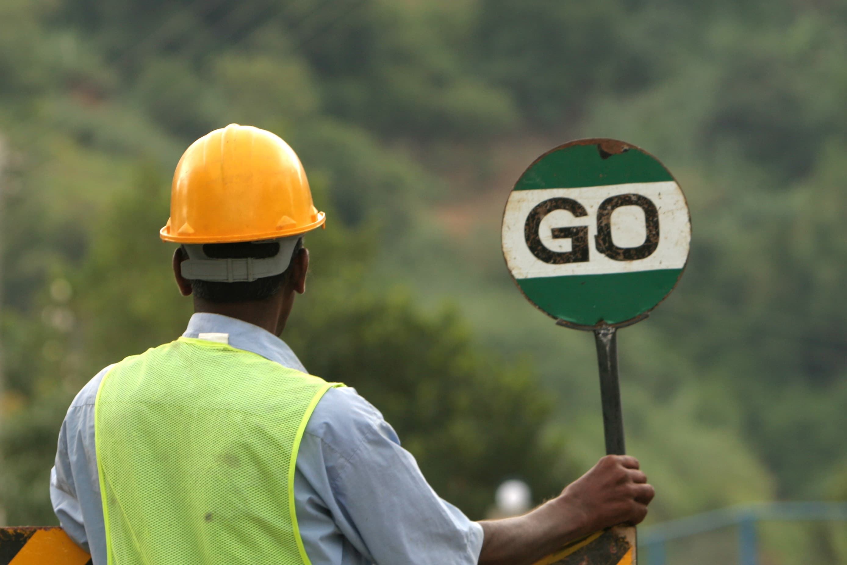 Workman holding 'Go' sign