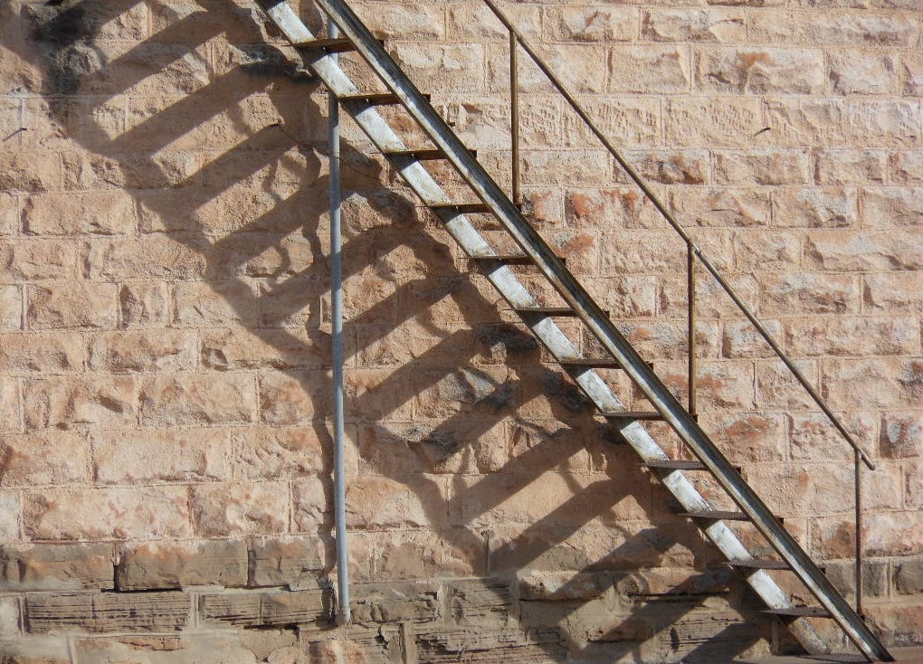 A set of metal steps going up the side of a brick wall.