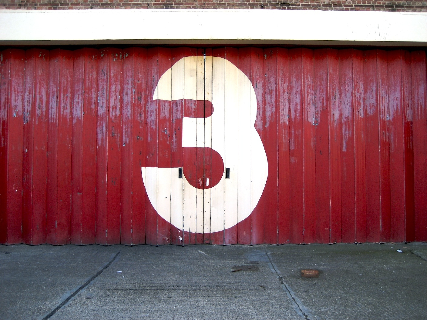 The number three painted on a garage door